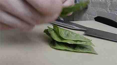 cortando hojas verdes en la cocina