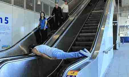 persona acostada sobre los descansa brazos de una escalinata electrica