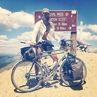 Benedict con su bicicleta y el equipo de camping